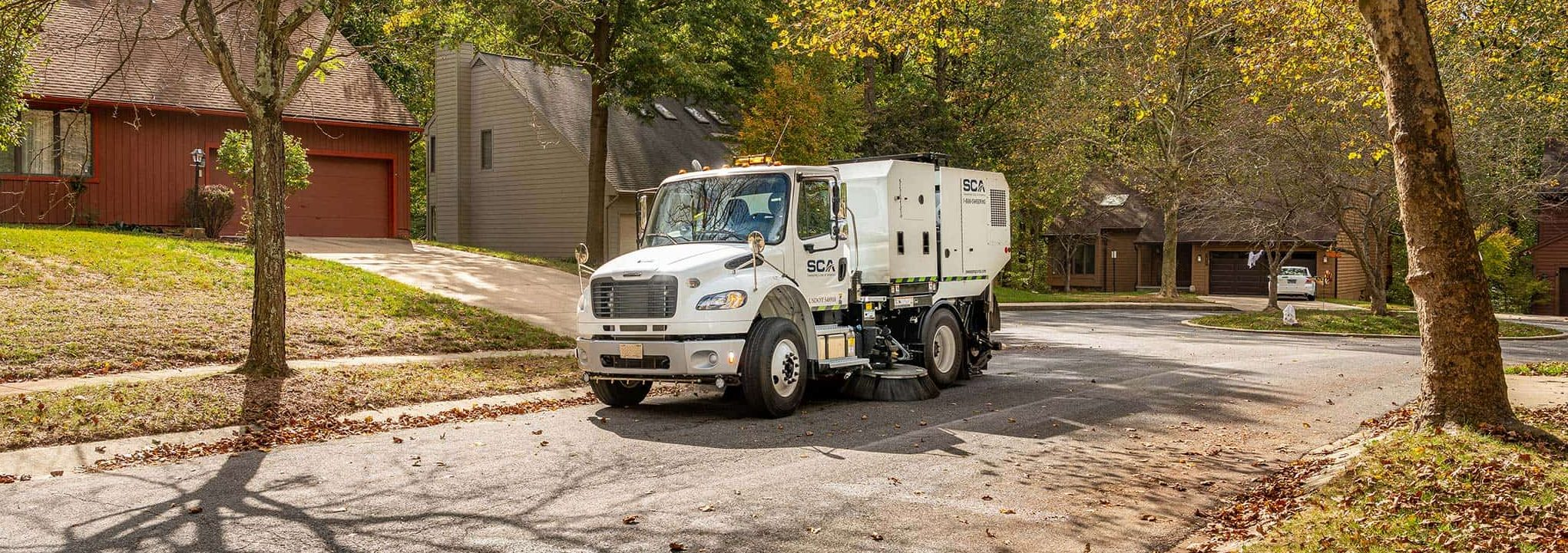 A sweeping truck cleaning a residential neighborhood
