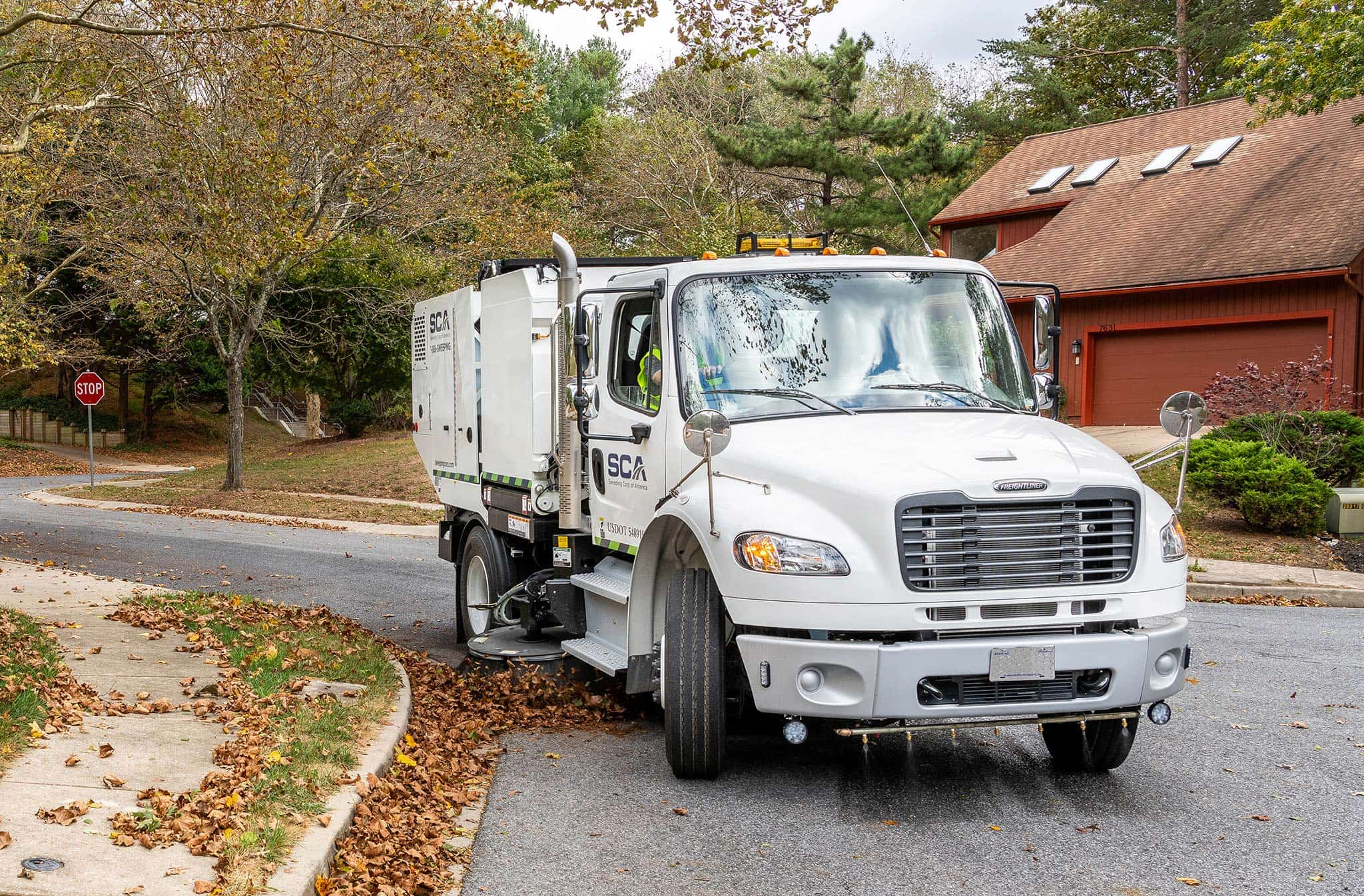 A sweeping truck cleaning leaves in a residential neighborhood